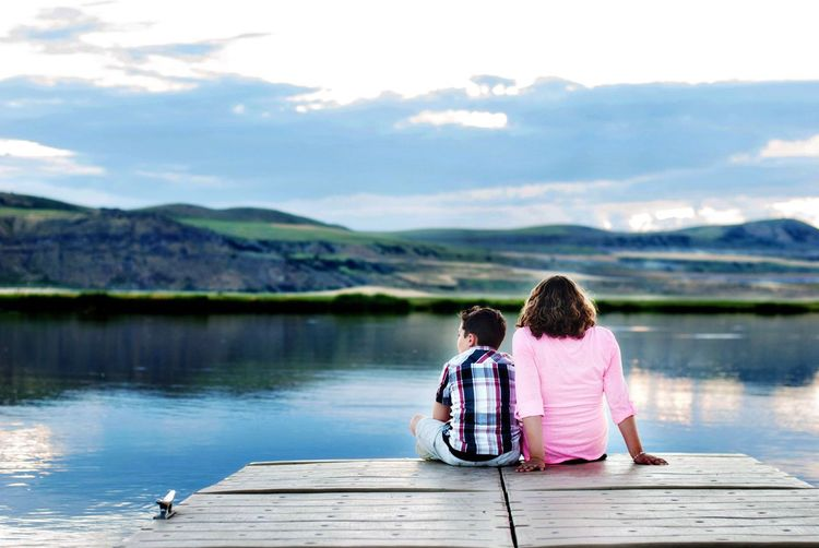 Rear view of siblings sitting on jetty at lakeshore