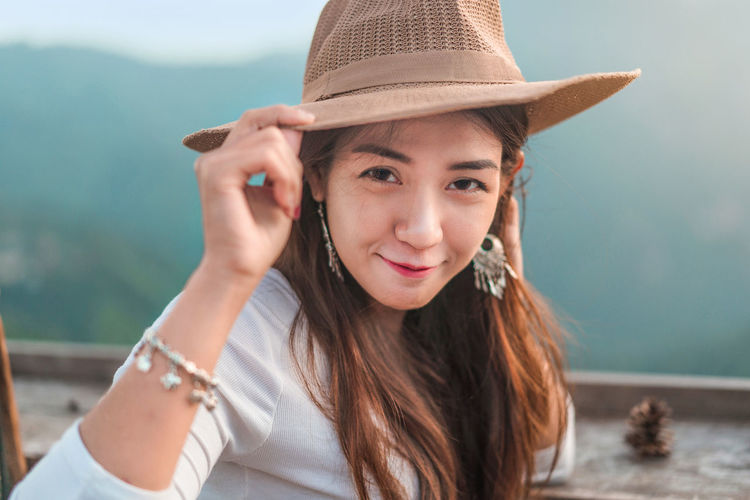 Portrait of smiling woman wearing hat standing outdoors