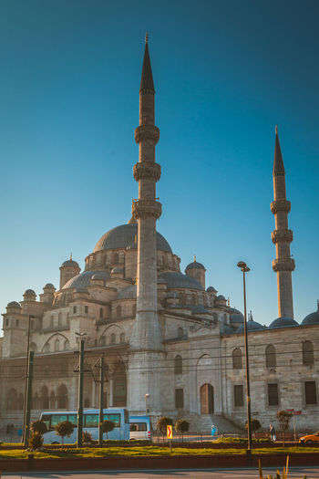 Exterior of new mosque against clear blue sky in city