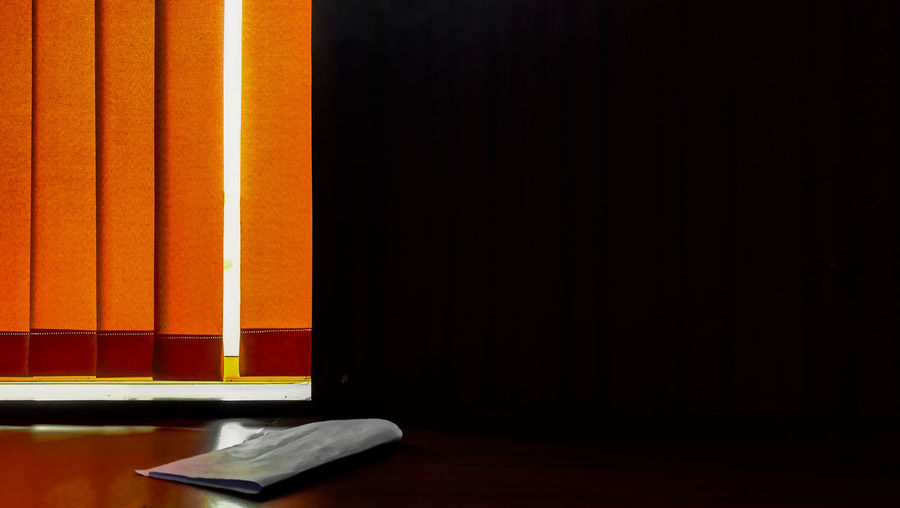 Orange blinds by black wall