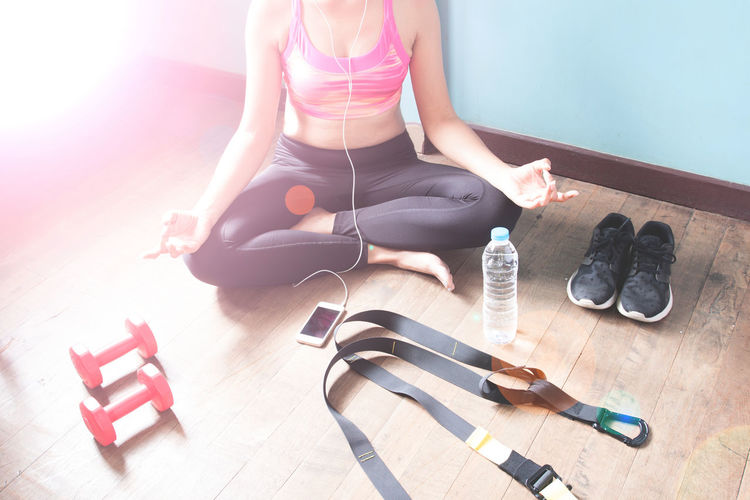 Low Section Of Woman Listening Music While Practicing Yoga