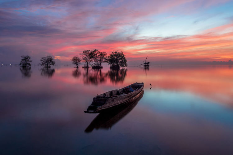 Boat in lake against sky during sunset