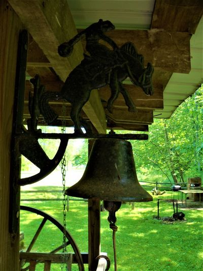 Cowboy Bell Bell Cowboy Indiana Porch Architecture Art And Craft Cabin Cabin In The Woods Country Life Creativity Day History Horse Human Representation Male Likeness Mammal Metalwork Nature No People Plant Representation Sculpture Seat Statue The Past