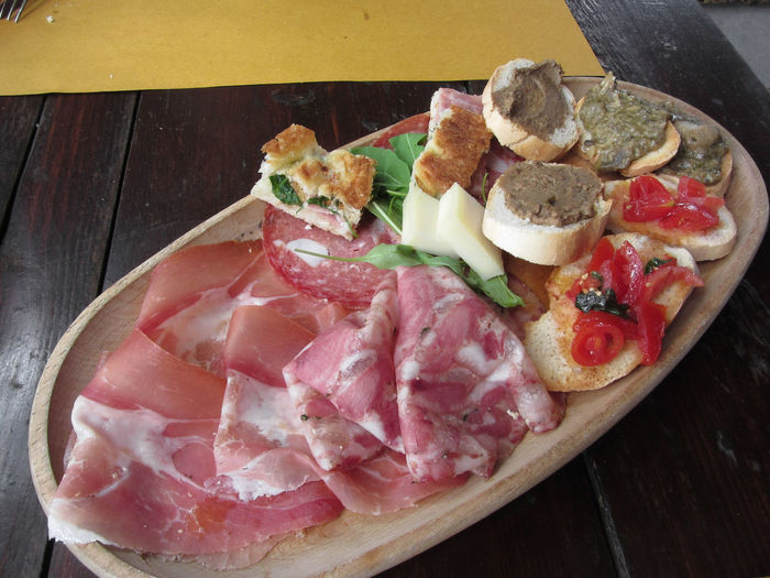 Typical rustic tuscan appetizer with crostini, prosciutto, brawn, salami, cheese on a wooden tray . Italian starter Antipasto Pecorino Rustic Snack Tray Tuscan Tuscany Appetizer Brawn Bread Cheese Cold Cuts Crostini Ham Head Cheese Italian Food Meat Pork Prosciutto Salami Salumi SLICE Starter Variety Wooden