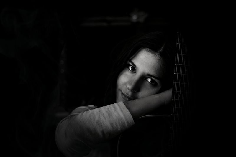 Close-up portrait of young woman with guitar against black background