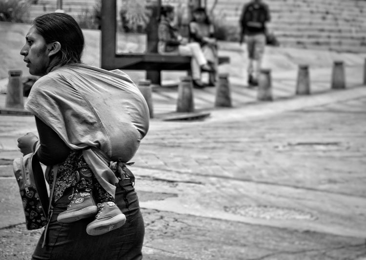 Rear view of woman carrying child while walking outdoors