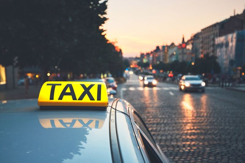 Taxi car on the city street at dusk. Business Capital Cities  Car City City Life Dusk Evening Illuminated Land Vehicle Moody Sky Outdoors Prague Road Sign Street Streetphotography Sunset Taxi Traffic Transportation Travel Travel Destinations Wenceslas Square Yellow