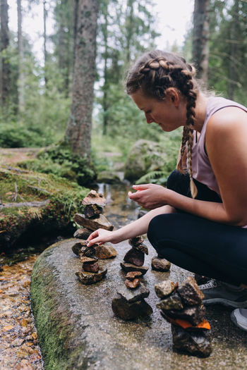 Side view of woman sitting on land in forest