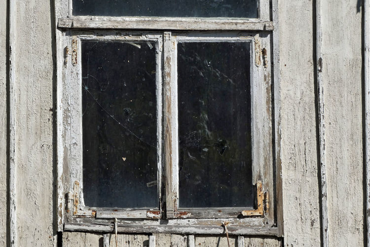 Closed window of old abandoned house