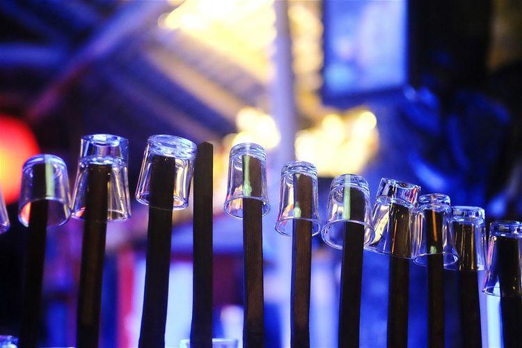 Shot glasses on bamboos at illuminated bar