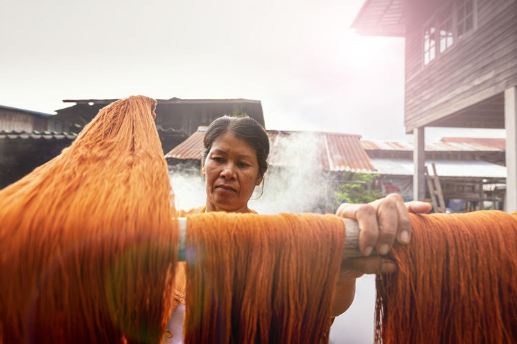 Woman hanging wool on wood outdoors