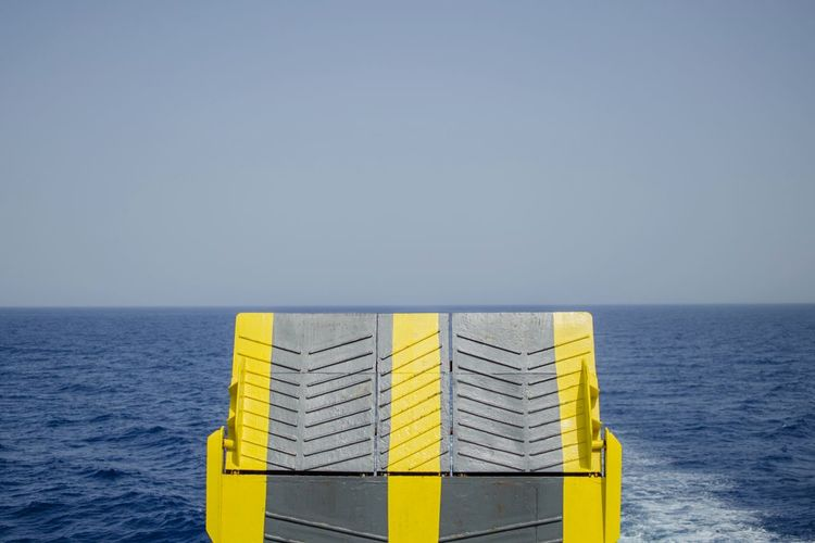 Cropped image of ferry ramp on sea against clear sky