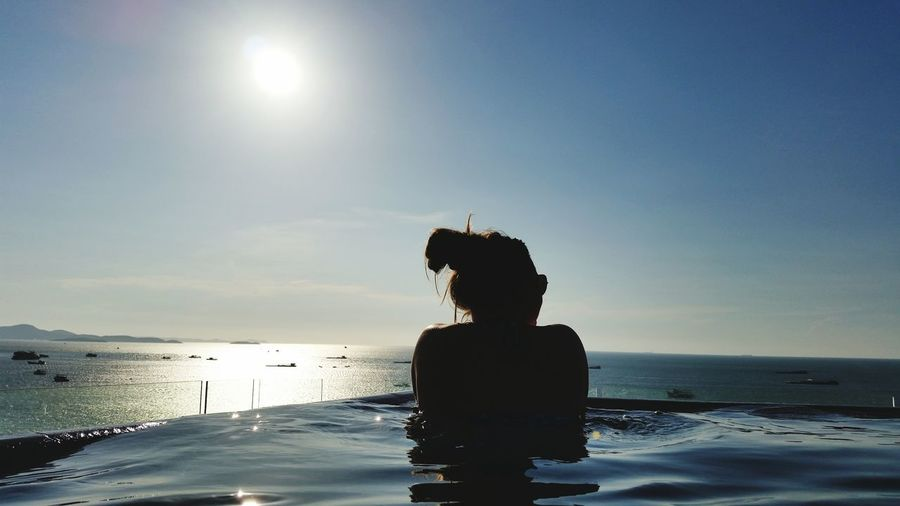 Rear view of silhouette woman swimming in infinity pool by sea during sunny day
