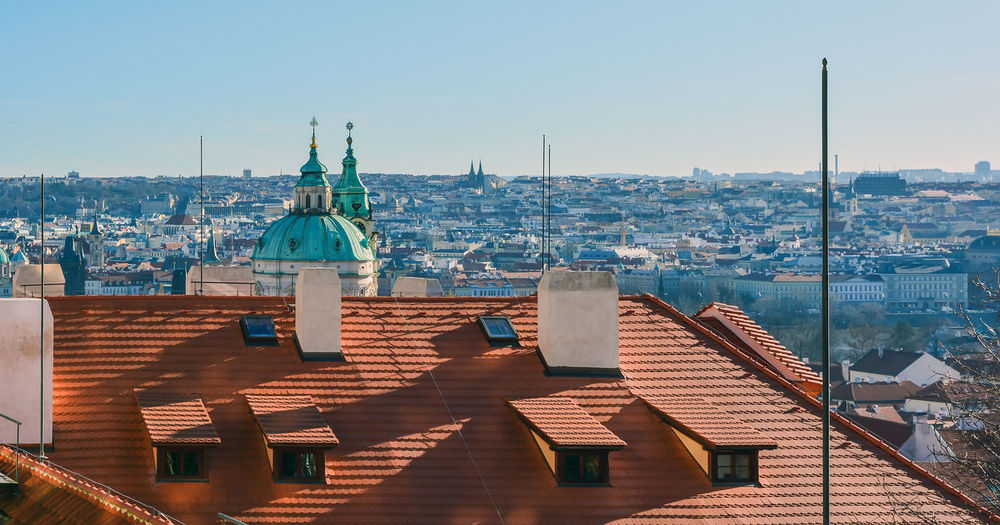 Cityscape of prague with cathedral of st. nicholas at sunny day, with red roof in the foreground.