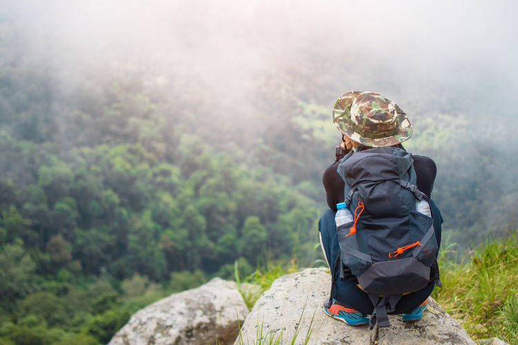 Rear view of boy on cliff against forest