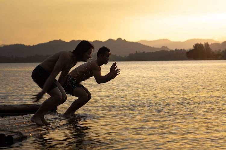 Shirtless men jumping in lake against sky during sunset