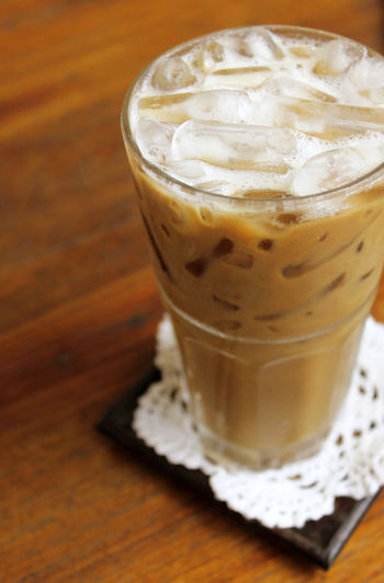 Food And Drink Drink Refreshment Glass Drinking Glass Coffee - Drink Latte Coffee Table Household Equipment Cold Temperature Indoors  Wood - Material Frozen Food Iced Coffee Hot Drink Cold Drink High Angle View Close-up Ice Cube No People Breakfast Wood Grain Ice Coffee
