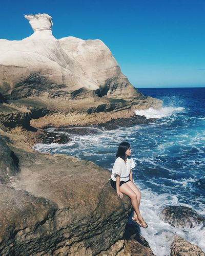Young Woman Sitting On Rock Formation While Looking At Sea Against Sky