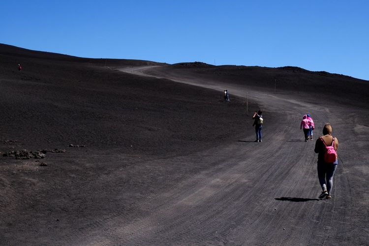 Rear view of people hiking at mount etna