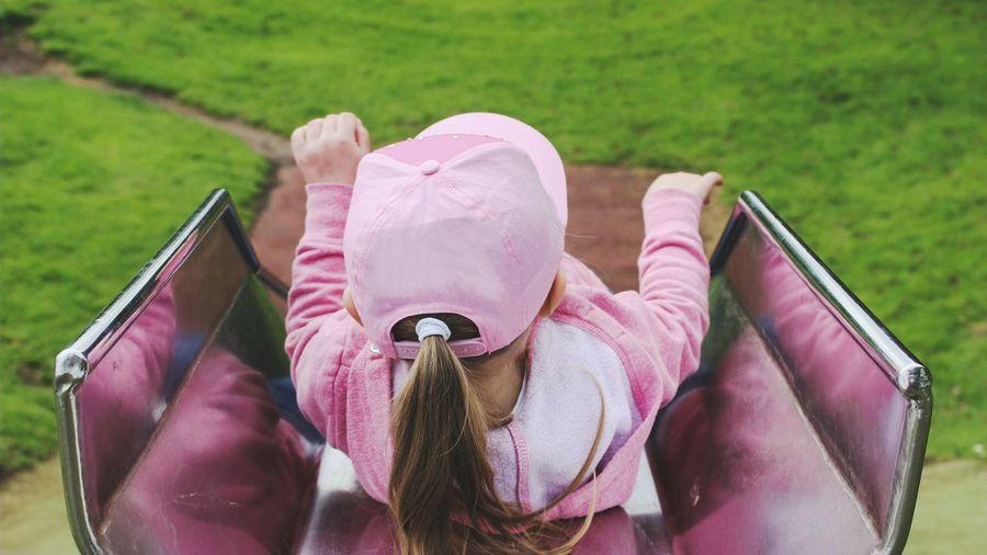 High Angle View Of Girl Sliding On Slide At Playground