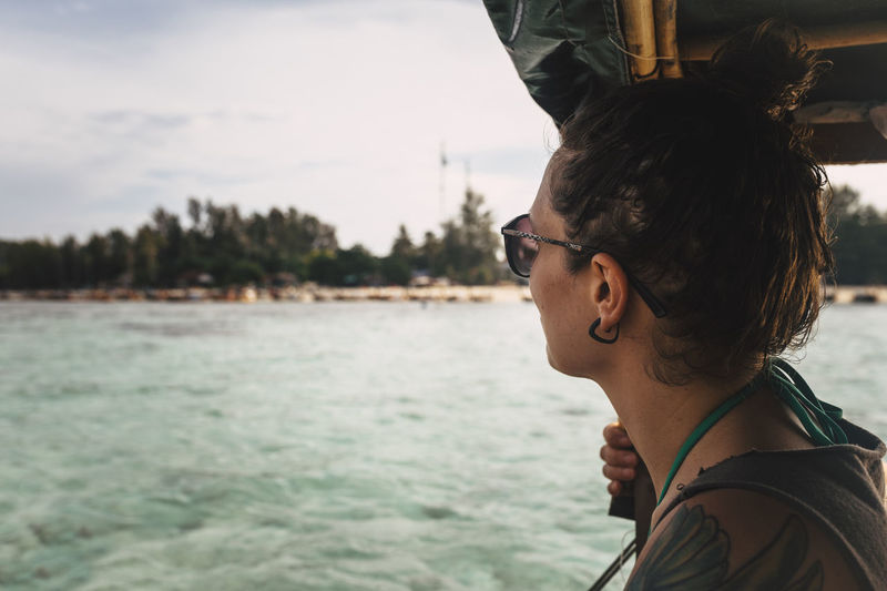 Side view of young woman wearing sunglasses against sea