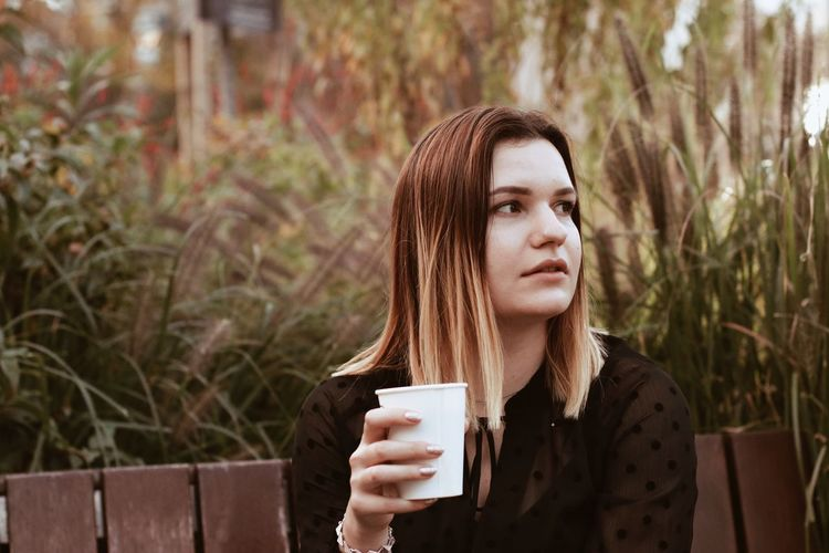 Young woman looking away while drinking coffee against plants