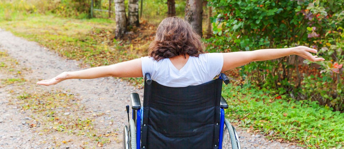 Rear view of woman sitting on wheelchair outdoors