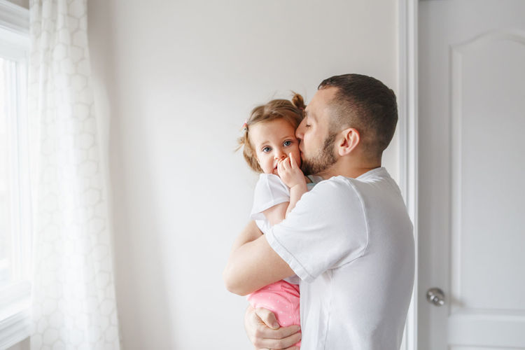 Side view of man kissing daughter at home