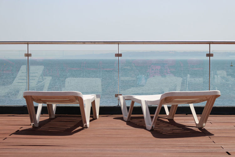 Deck chairs in ship against railing in front of sea