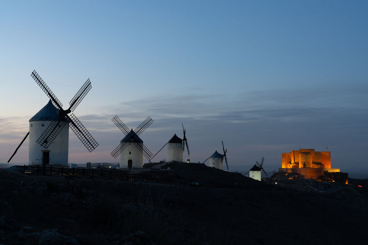 Traditional windmill on landscape against sky at sunset