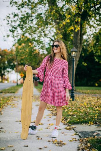Girl smiling wearing sunglasses standing on sidewalk holding a skateboard