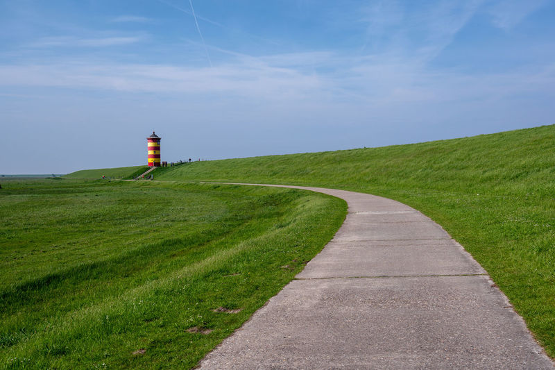 Road Leading Towards Lighthouse On Field Against Sky