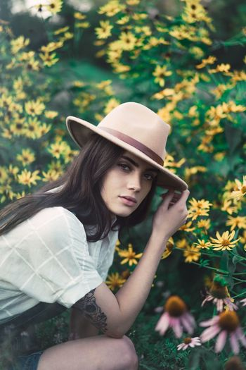 Hat Young Adult Young Women One Person Real People Flower Beautiful Woman Lifestyles Leisure Activity Fashion Day Casual Clothing Focus On Foreground Outdoors Beauty Standing Nature Women Portrait Beauty In Nature Paint The Town Yellow