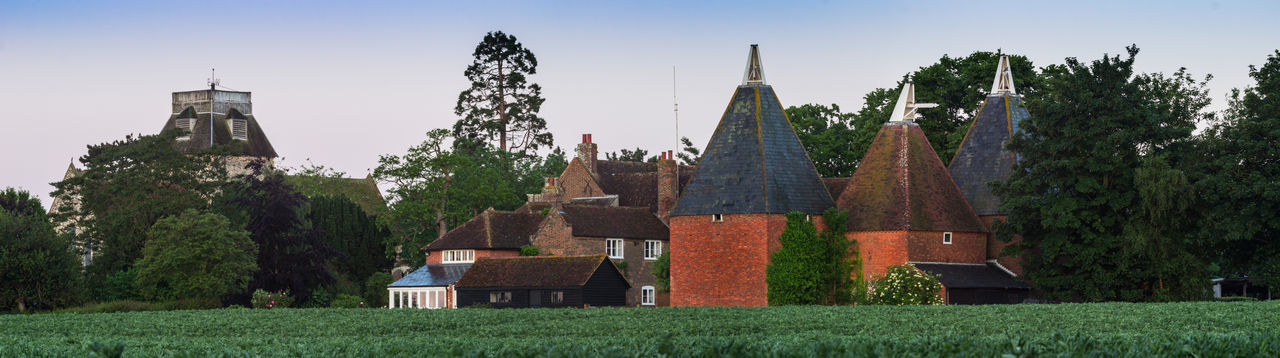 Oast house,Garden of England, Kent, England. Built Structure Architecture Building Exterior Plant Building Tree Place Of Worship Sky Religion Nature Spirituality Belief Grass Field No People Land Tower House Outdoors Spire  Oast House Hops Travel Destinations Tourism Getty Images History Vivid International Rural Scene Village Tranquil Scene Wheat Field Church Tower