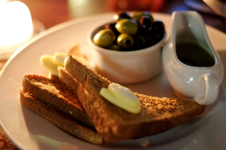 Close-up of toast and olives on table