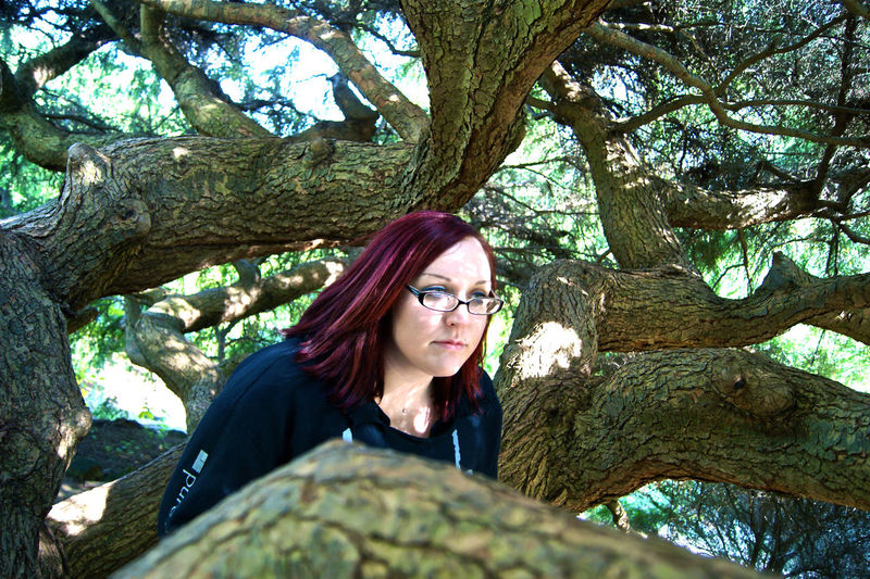 Thoughtful Young Woman With Dyed Hair By Tree Branches
