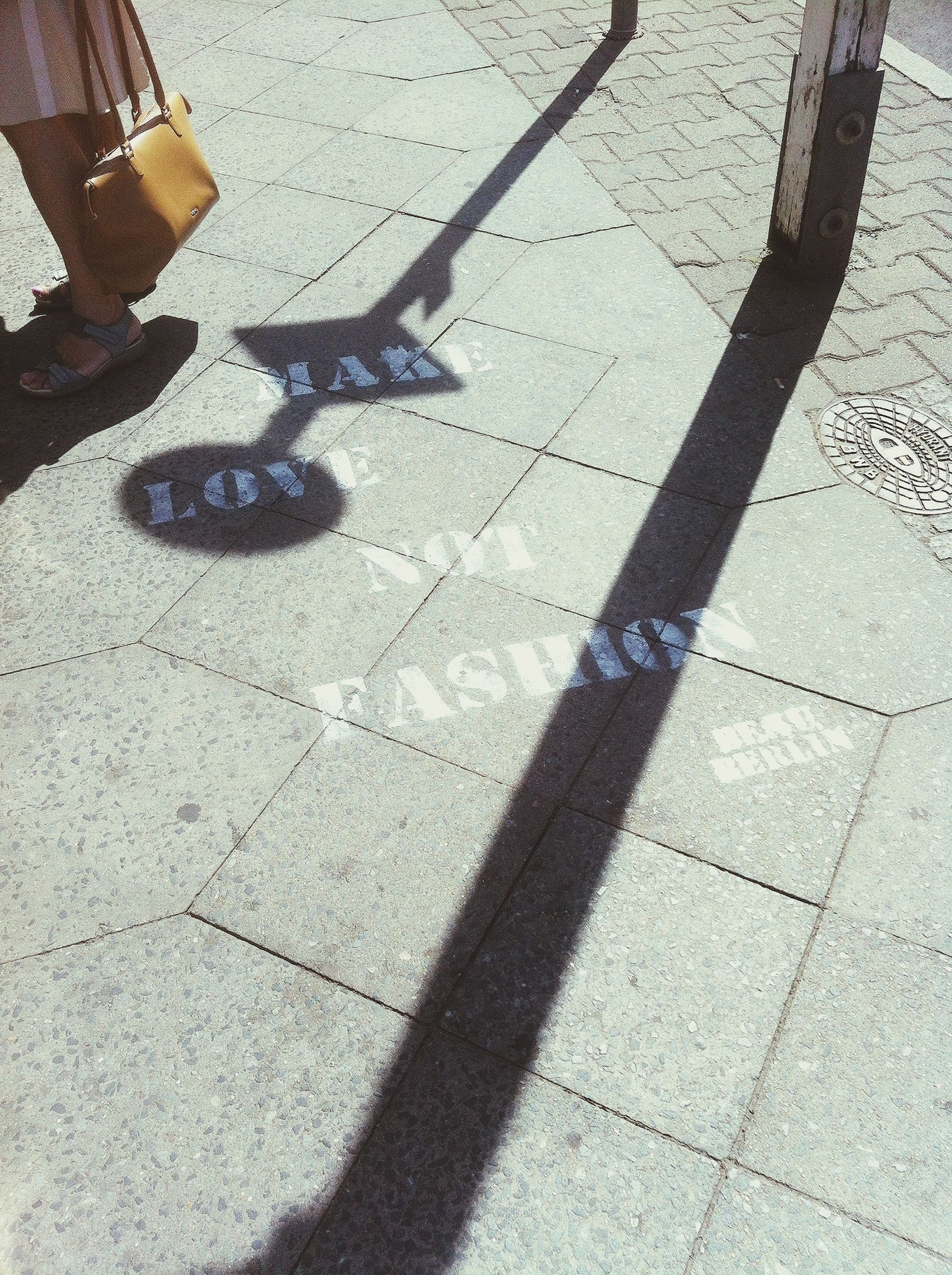 shadow, street, high angle view, sunlight, paving stone, cobblestone, sidewalk, footpath, road, focus on shadow, outdoors, day, pavement, unrecognizable person, road marking, transportation, lifestyles, walking