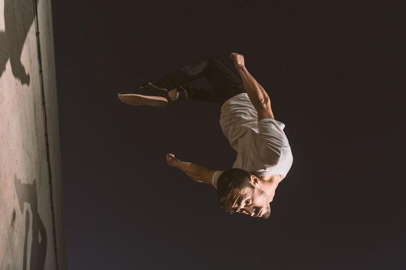 Full length of man jumping against sky at night