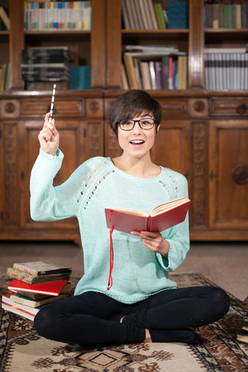 Young pretty woman student with books in the library Answer Beautiful Book Bookcase Brunette Caucasian Eyeglasses  Eyeglasses  Find Solution Girl Happiness Hintergrundgestaltung Library Looking At Camera One Person People Portrait Pretty Sitting Smiling Solution Student Student Life Studying Woman