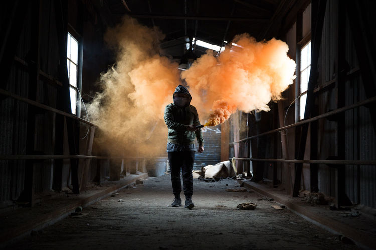Full length of man holding distress flare while walking in abandoned workshop