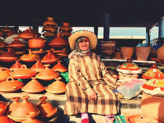Portrait of mature woman selling clay containers