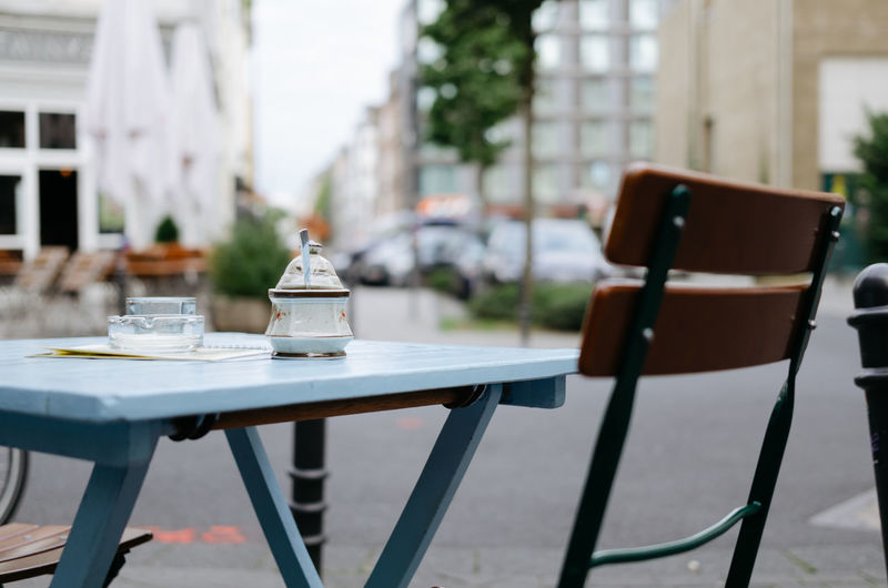 Empty chair and table at sidewalk cafe