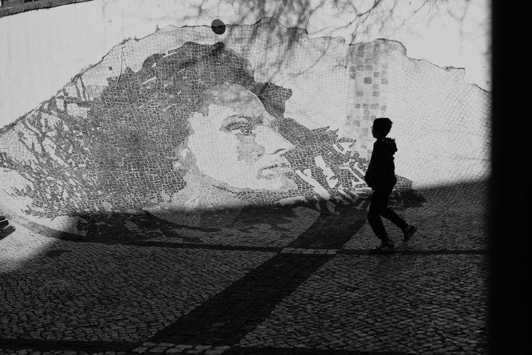 Shadow of man walking on footpath