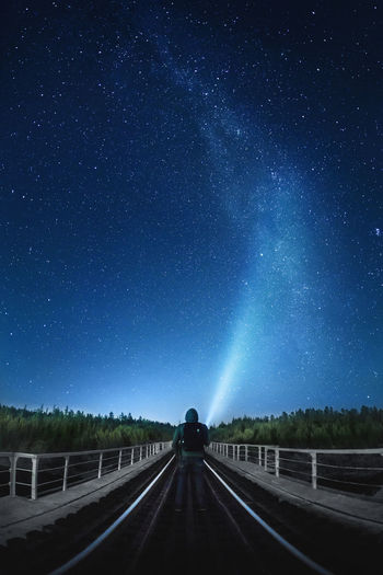 Rear View Of Person Standing On Road Against Starry Sky At Night