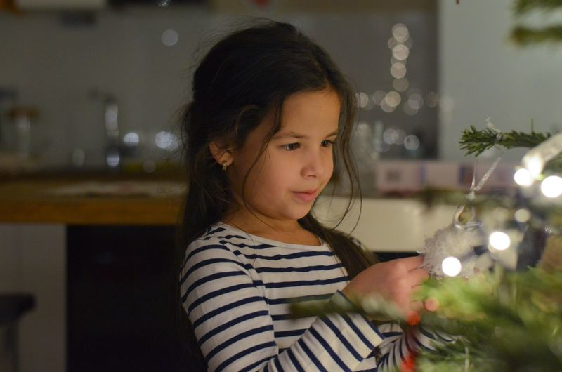 Close-Up Of Girl Holding Christmas Tree At Home