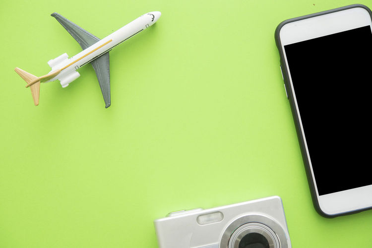Close-Up Of Mobile Phone With Airplane Over Green Background