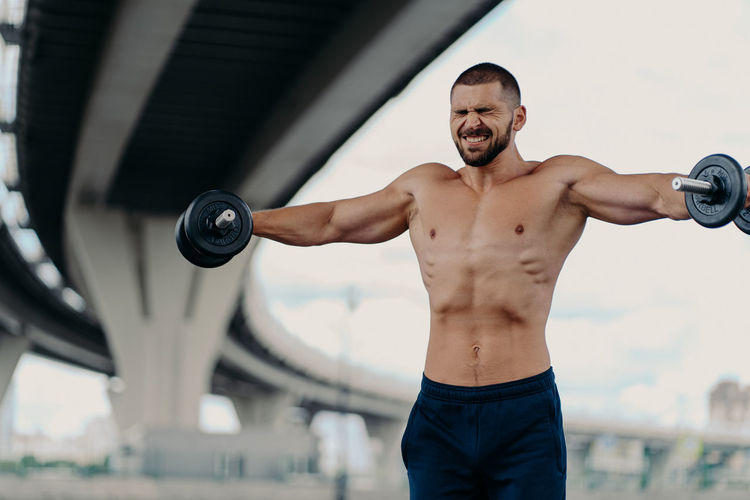 Shirtless man lifting dumbbells against bridge