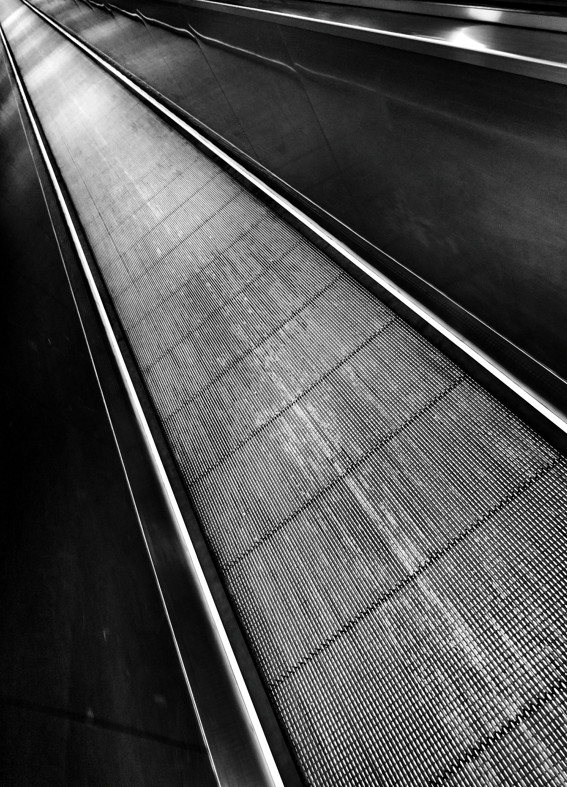 transportation, railroad track, high angle view, mode of transport, the way forward, road marking, diminishing perspective, indoors, road, rail transportation, pattern, vanishing point, on the move, public transportation, metal, travel, empty, no people, asphalt, speed