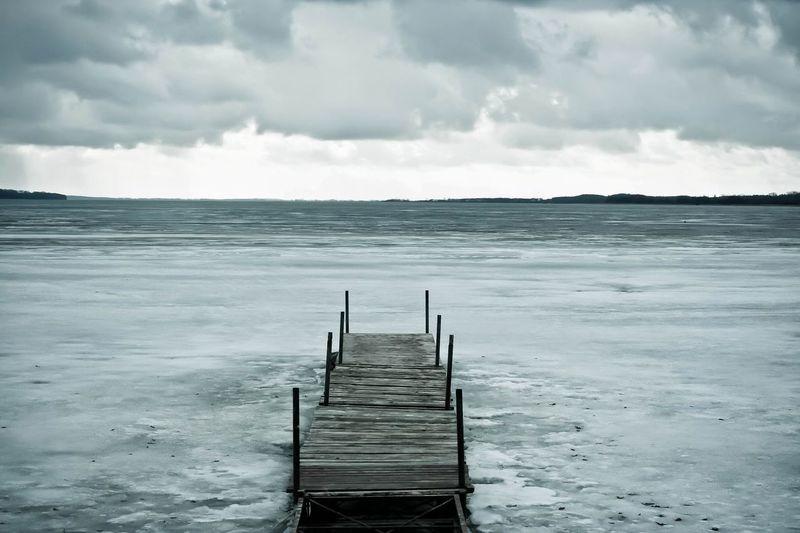 Wooden jetty on frozen sea