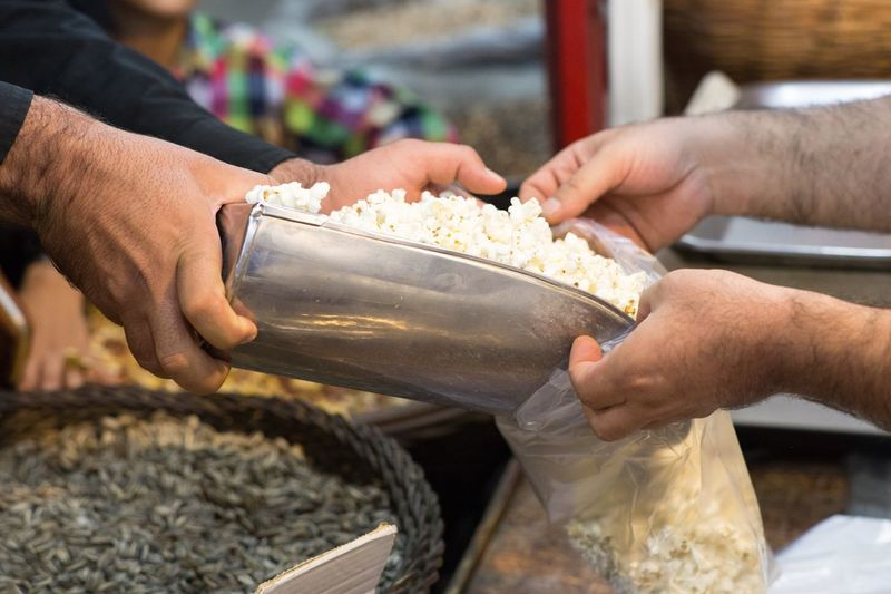 Cropped Hand Of Vendor Selling Popcorns To Customer At Market